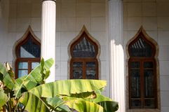 Green plant leaves in front of an Arabic Building Facade. Kunming, Yunnan, China Royalty Free Stock Photo
