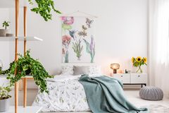 Green plants on shelves beside a bed dressed in white cotton bedding and teal blue blanket in a bright bedroom interior. Flowers and birds painted on the stock photography