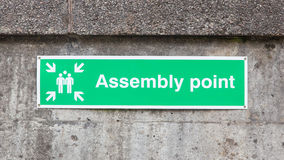 Green plastic 'assembly point' sign. Isolated on concrete wall Stock Photo