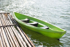 Green plastic boat parked at bamboo raft on water surface. this Stock Photos