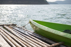Green plastic boat parked at bamboo raft on water surface. this Stock Images