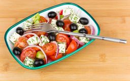 Green plastic bowl with Greek salad and fork  on board Royalty Free Stock Photos