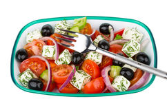 Green plastic bowl with Greek salad and fork Stock Image
