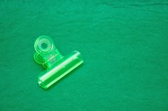 A green plastic bulldog clip. On a green background royalty free stock image
