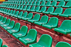 Green plastic chairs on  football tribune Royalty Free Stock Image