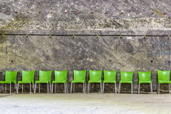 Green plastic chairs. In raw near a wall in a salt mine Stock Image