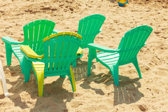 Green plastic chairs on sand. Stock Photos