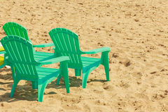 Green plastic chairs on sand. Royalty Free Stock Photography