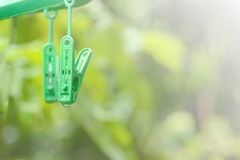 Green plastic clothespin clip with water drop. Royalty Free Stock Photography