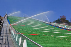 Green plastic coating of a ski jump hill in RusSki Gorki Jumping Center is under summer maintenance with flushing water. Watering. Sochi, Russia - February 8 Stock Photos