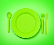 Green  plastic disposable tablewar. Bright green  plastic disposable tableware, plates and forks, on bright green background Stock Photos
