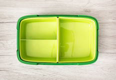 Green plastic food box on the wooden background. Green plastic box for food storage on the wooden background Stock Images