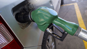 Green plastic fuel gun filling the gasoline tank Royalty Free Stock Photography