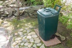 Green plastic garbge bin in garden.Single garbage container stand in park.  Stock Image