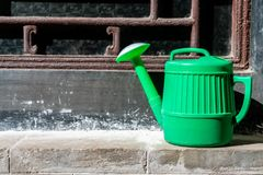 A green plastic kettle. Plastic water bottles by the window royalty free stock photography
