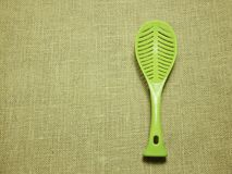 Green plastic ladle on sackcloth woven background royalty free stock photo