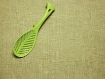 Green plastic ladle on sackcloth woven background stock images