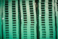 Green plastic pallets in warehouse. Stock Photos