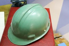 Green plastic safety helmet for the worker. Protective helmet to protect the head of people operating in hazardous conditions stock photos