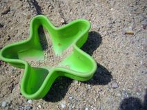 Green plastic sand toy shaped like a starfish lying in the sand stock image