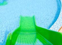 Green plastic slider. In front of swimming pool Royalty Free Stock Images