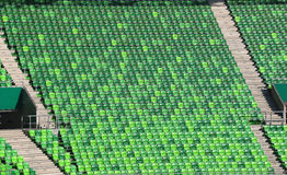 Green plastic stadium chairs on bleachers in row Royalty Free Stock Image