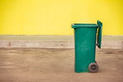 Green plastic trash container on wheels on the background of a y. Ellow wall Royalty Free Stock Image