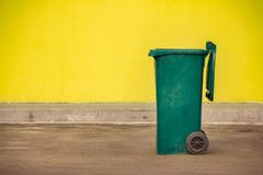 Green plastic trash container on wheels on the background of a y. Ellow wall Stock Photography