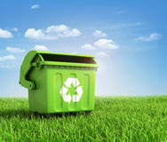 Green plastic trash recycling container. Ecology concept, with landscape background Royalty Free Stock Photo