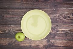 Green plate and 1 apple on table.  royalty free stock photo