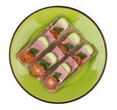 Green plate with crisp bread with bacon, cucumbers and tomatoes Royalty Free Stock Images