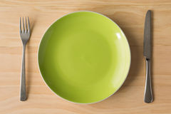 Green plate with fork and knife Royalty Free Stock Photo