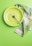 Green plate with fork and napkin on green background above view Royalty Free Stock Photo