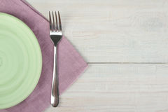 Green plate, fork and purple napkin Stock Images