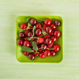 Green plate with fresh cherry and raspberries on the green wooden background, top view. Square photo Stock Photos