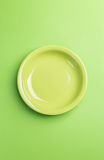 Green plate on green background,above view.Useful as a food back Stock Photography