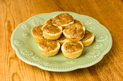 Green plate of pecan tassie cookies. On wooden table Royalty Free Stock Photo