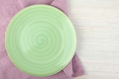 Green plate on a purple napkin Stock Photography