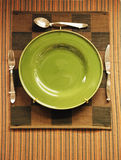 Green plate for sale. Green plate on the cloth for sale with knife,fork,and spoon Royalty Free Stock Photography