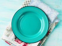 Green plate on Vintage napkin wooden textured background Stock Photos