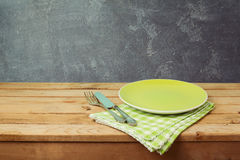 Green plate on wooden table over blackboard background. Dinner setting Stock Photography