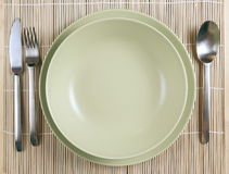 Green plates with knife and fork and spoon Stock Photos