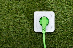 Green plug in outlet on grass Stock Photo