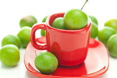 Green plum  in the cup Royalty Free Stock Photography