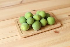 Plum fruits on wooden table. Green plum fruits on wooden table royalty free stock photo