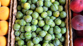 Green Plums. Crate of green plums for sale in a market in San Sebastian, Spain Stock Image