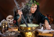 Green poison. Halloween witch stirring in green poison soup in her cauldron royalty free stock photo