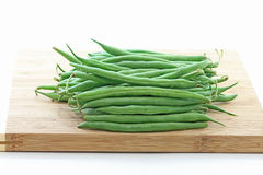 Green Pole Beans on Bamboo Chopping Board. Bunch of fresh whole green pole beans on top of wood chopping board, with white background stock images