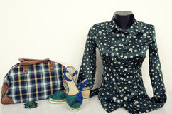 Green polka dots shirt on mannequin with matching accessories. Cute blouse on tailor's dummy with purse, shoes and jewellery Stock Photo