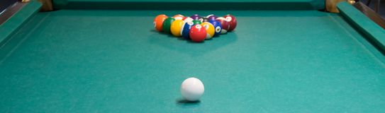 Green pool table, pyramid of balls to play, white ball to hit. royalty free stock photo